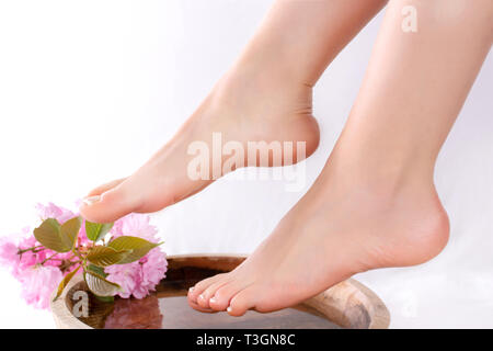 Girl legs and feet with french pedicure in beauty and spa studio on wooden bowl with water and decoration pink flower. Female beauty and spa concept - Stock Image