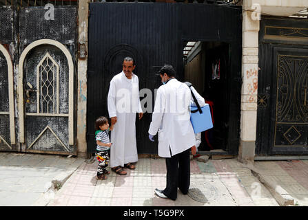 Sanaa, Yemen. 24th Apr, 2019. A medic talks to a father before giving him and his children anti-cholera vaccines in Sanaa, Yemen, on April 24, 2019. Yemeni Health Ministry in collaboration with WHO and UNICEF launched a 6-day home-to-home emergency immunization campaign against cholera in three most seriously affected districts in Sanaa with an aim to target all people from age of one year and above except pregnant women. Credit: Mohammed Mohammed/Xinhua/Alamy Live News - Stock Image