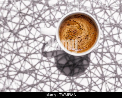 White coffee cup on abstract background top view. Sparse composition with copy space - Stock Image