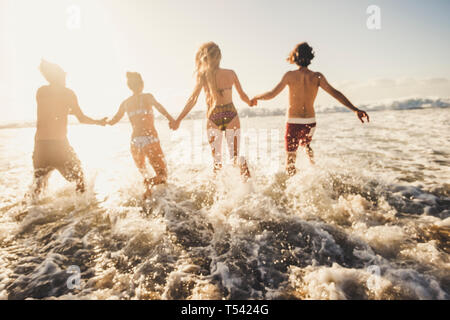 Defocused for active and motion concept people have fun running in the sea water during summer vacation - group friends together enjoy happiness - act - Stock Image