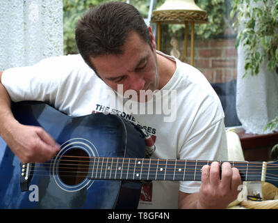 Brown haired man playing guitar - Stock Image