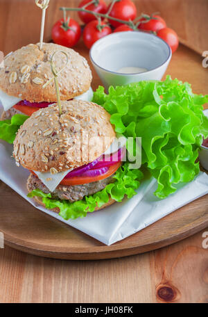 Cheeseburger with salad, onion, tomato and fresh bread - Stock Image