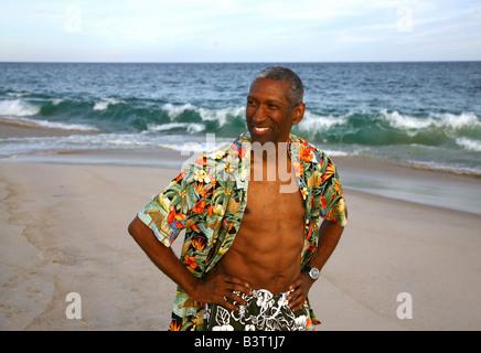 Mature African American man walking on beach - Stock Image