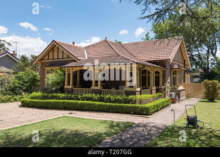An Australian brick and tile federation home with a return front veranda and a well kept front yard and garden in Sydney - Stock Image