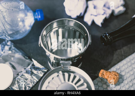 open empty garbage bin surrounded by reusable waste materials like plastic paper and glass, concept of reducing damage to the environment - Stock Image
