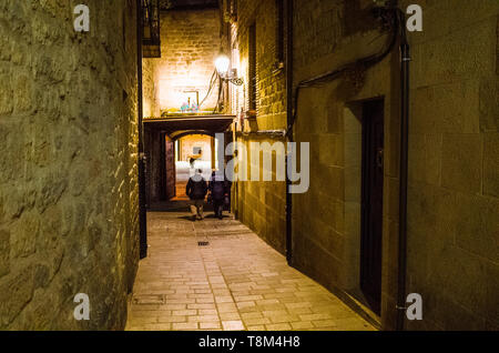 Laguardia, Álava province, Basque Country, Spain : A man and a woman walk under an arch at a narrow alley illuminated at night in the historic town of - Stock Image