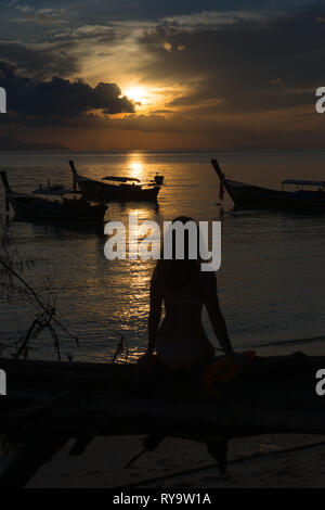 Silhouette of a girl sitting on a fallen tree on Sunrise beach against rising sun, Ko Lipe, Thailand - Stock Image