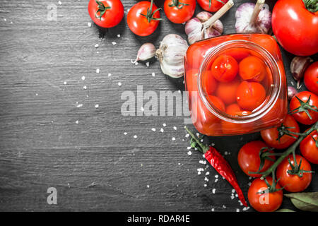 Pickled tomatoes with garlic and herbs. On black background. - Stock Image