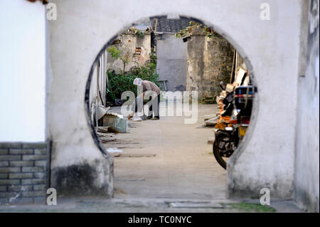Tongli, China- November 28, 2008: Old lady street sweeper cleaning the street in a hutong of the town - Stock Image