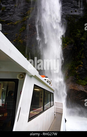 View from boat on Milford Sound, New Zealand. The front of the boat is taken very close to the waterfall. - Stock Image
