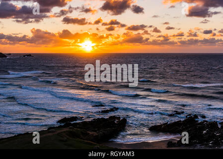 Sun setting over waves and surf at Fistral Beach, Newquay, Cornwall, UK - Stock Image