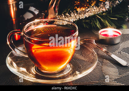 Tea in glass cup close up; Christmas decorated - Stock Image