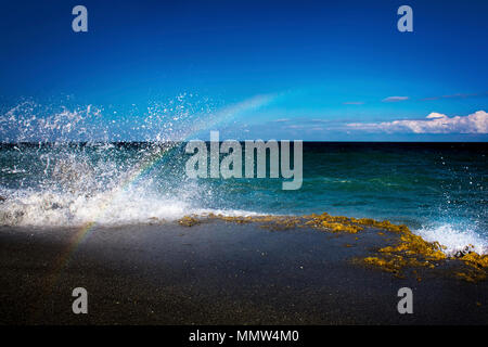 Crashing waves at Blowing Rocks Preserve in Florida create a momentary rainbow. - Stock Image