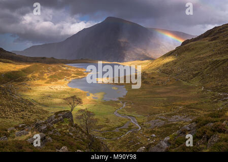 Rainbow passing over Cwm Idwal in the mountains of Snowdonia National Park, North Wales. Autumn (September) 2017. - Stock Image