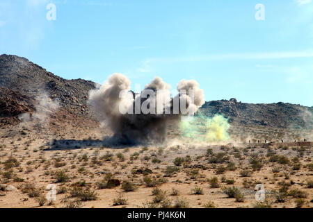 Impact from an Anti-Personnel Obstacle Breaching System (APOBS) throws up a large plume near an objective during live-fire training conducted by India Company, 3rd Battalion, 4th Marines, 7th Marine Regiment, in the Galway Lake Training Area in the Johnson Valley Exclusive Military Use Area, Marine Corps Air Ground Combat Center, Twentynine Palms, Calif., Aug. 24, 2018. (Marine Corps photo by Kelly O'Sullivan) - Stock Image