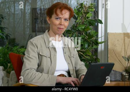 Adult woman over 40 using laptop at home in 2003 and look at camera. - Stock Image