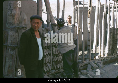 Street scene of men building a wall of brick and mortar; Bukhara, Uzbekistan, former USSR. - Stock Image