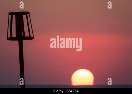 sunrising over coast showing silhoutted marker basket - Stock Image