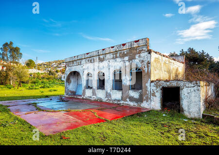 Exterior of an abandoned old building and coal bin in a rural meadow field. - Stock Image