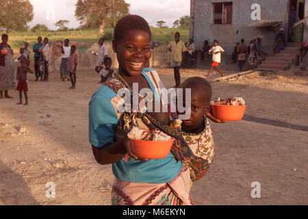 Floods in Mozambique  March 2000; A young mother happy to have received cooked bowls of rice and stew made with - Stock Image