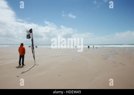 A male lifeguard standing by a black and white chequered RNLI beach safety flag keeping a lookout on Croyde Bay - Stock Image
