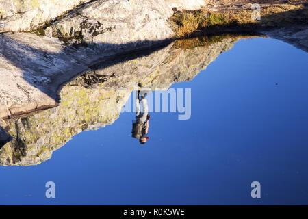 Upside Down Hiker Silhouette Reflected in Still Water of granite fissure on Mount Seymour Peak, North Shore Mountains above Vancouver, BC Canada - Stock Image
