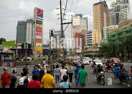 Pedestrians cross at a busy intersection in Makati City, Metro Manila, Philippines. - Stock Image