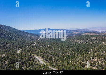 White Ribbon of forest highway leads through California hills. - Stock Image