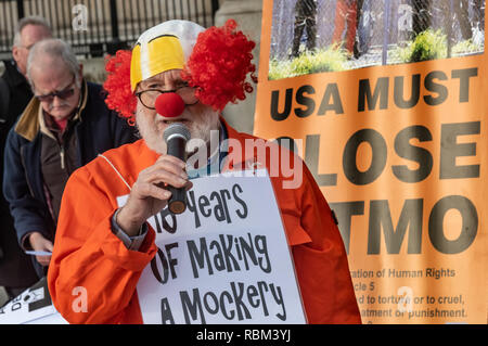 London, UK. 11th January 2019. A man in a clown headress speaks  at the protest  by the Guantanamo Justice Campaign and London Guantanamo Campaign marking the 17th anniversary of the first prisoners arriving at the illegal US camp. A display of posters, photographs of the remaining detainees, readings and speeches in Trafalgar Square highlighted the abuse, torture, lack of human rights, force-feeding and indefinite detention there. Credit: Peter Marshall/Alamy Live News - Stock Image