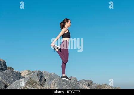 woman doing a leg stretch warm up exercise outside on rocks with blue sky - Stock Image