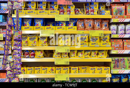 Multiple shelves full of a variety of sweets on display in store. B&M discount store, UK - Stock Image