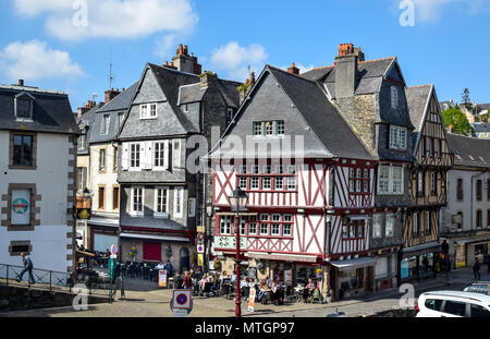Within a half-timbered building on a busy corner, a lively cafe full of people in Morlaix, Brittany, France. - Stock Image