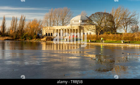 Newcastle, England, UK - February 6, 2019: A cyclist rides past the art deco Palace of Arts building and frozen lake on a winter day in Exhibition Par - Stock Image