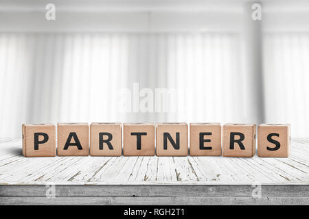 Partners sign on a desk in a bright office with white curtains in the background - Stock Image