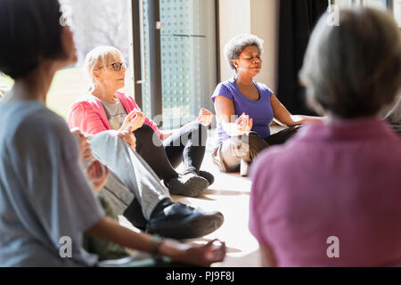 Serene active seniors meditating in circle - Stock Image
