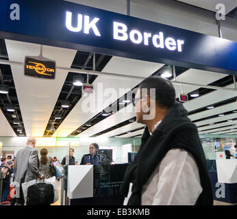 UK Border control checking passports at Heathrow airport in Britain - Stock Image