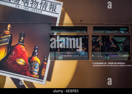 Passengers travelling on a Hong Kong tram advertising spirits - Stock Image