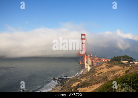 Coastal bluffs on a clear day with fog rolling through the Golden Gate Bridge beyond, San Francisco California, - Stock Image