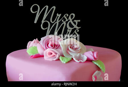 A wedding cake with 'Mrs and Mrs' cake decoration - Stock Image
