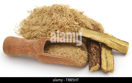 Liquorice stick and ground in a wooden scoop over white ackground - Stock Image