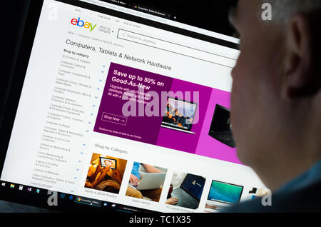 Man sitting at a computer monitor browsing through the Internet looking at the Ebay UK website on the World Wide Web using an Internet Browser. - Stock Image