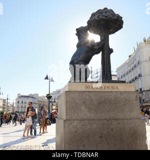People Embracing Under the Bear Statue in Puerta del Sol at Sunset - Stock Image