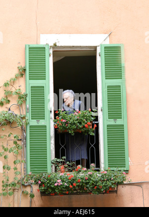 Elderly woman watching the world go by from her balcony - Stock Image