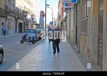 Elderly senior gentleman flaneur wearing a grey suit strolling along Rua da Cedofeita looking at neighbourhood Porto Portugal KATHY DEWITT - Stock Image