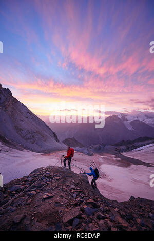 Hikers climbing rock at sunset, Mont Cervin, Matterhorn, Valais, Switzerland - Stock Image