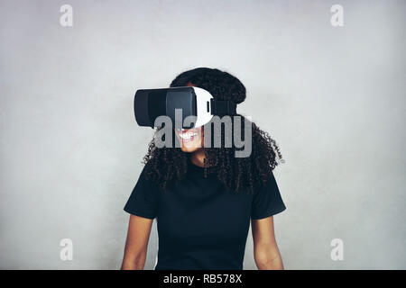 A beautiful young black woman with curly afro hair wears virtual reality VR headset and plays videogames while smiling in studio with grey background - Stock Image