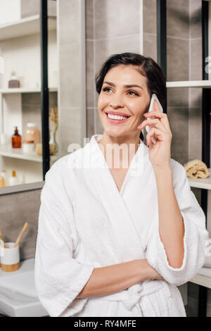 woman in bathrobe talking on smartphone in bathroom - Stock Image