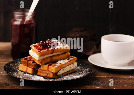 Viennese waffle in cherry syrup on a dark background with cup of tea - Stock Image
