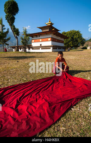 Young Buddhist monk spreads his crimson robe out to dry on the grass in front of Chimi Lhakhang near Punakha in - Stock Image