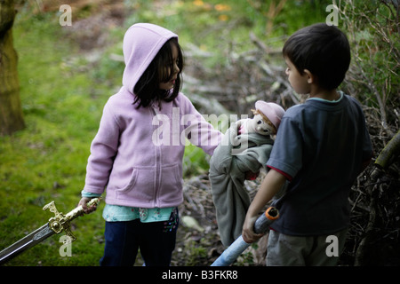 Girl aged five discusses an imaginary enemy with her six year old brother while handing over her toy doll - Stock Image